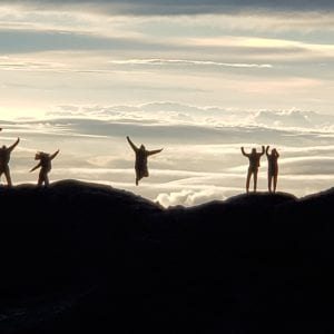 International research experience participants jumping on top of a mountain summit