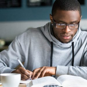 college age african american man writing notes at coffee shop
