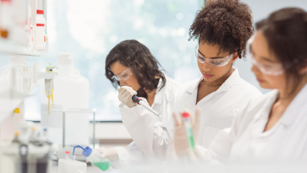 group of diverse female college students working in science lab