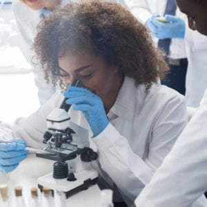 african american female college student looking into microscope in science lab